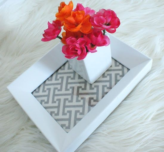Put fabric under the glass of an inexpensive picture frame to create a tray - cute for a bathroom.