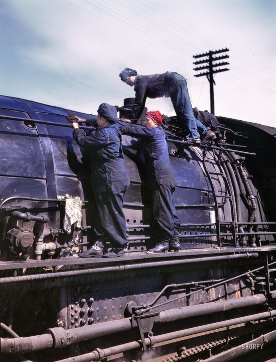"""Clinton, Iowa. April 1943. """"Chicago & North Western Railroad. Women wipers at the roundhouse cleaning one of the giant H-class locomotives."""" In the red bandanna: Marcella Hart, seen here in a few other posts. 4x5 Kodachrome transparency by Jack Delano for the Office of War Information."""
