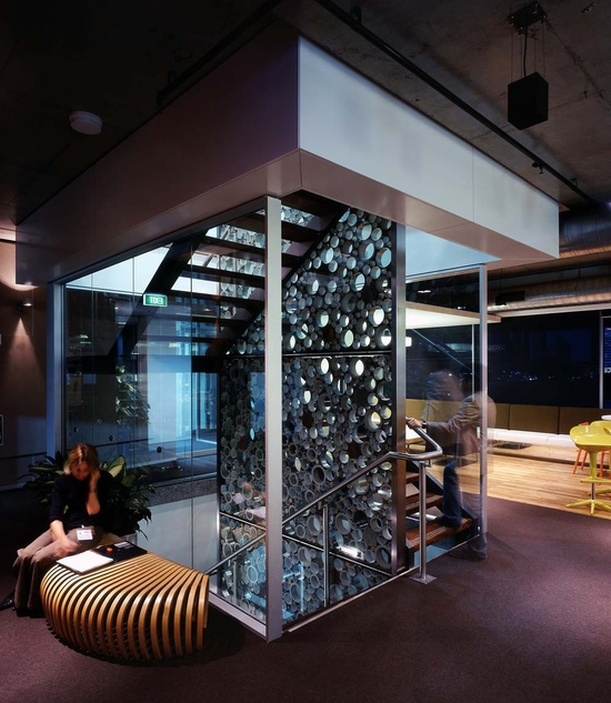 Glass stairwell with perforated separating wall.