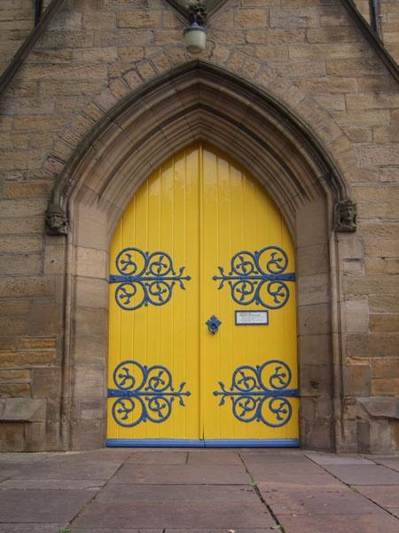 Great Parish Church Doors, Yellow with big blue door hinges.