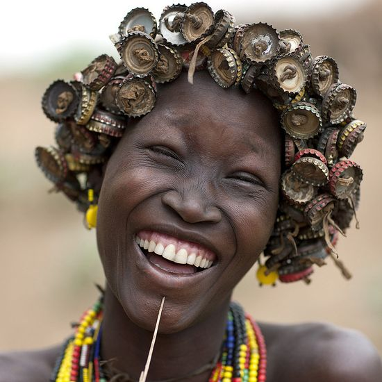 The Daasanach people (Ethiopia) collect the caps of the Coca and beers and make wigs with them. Ain't this a beauty!