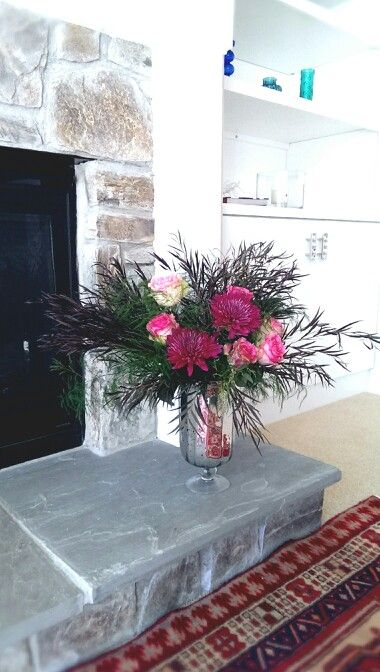 Flower arrangement by fireplace
