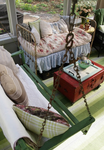 antique bed & vintage porch swing provide stylish & comfortable seating; red-painted vintage footlocker/trunk (on wheels) for storage coffee table --   Flea Market Styled Porch from The Painted Home