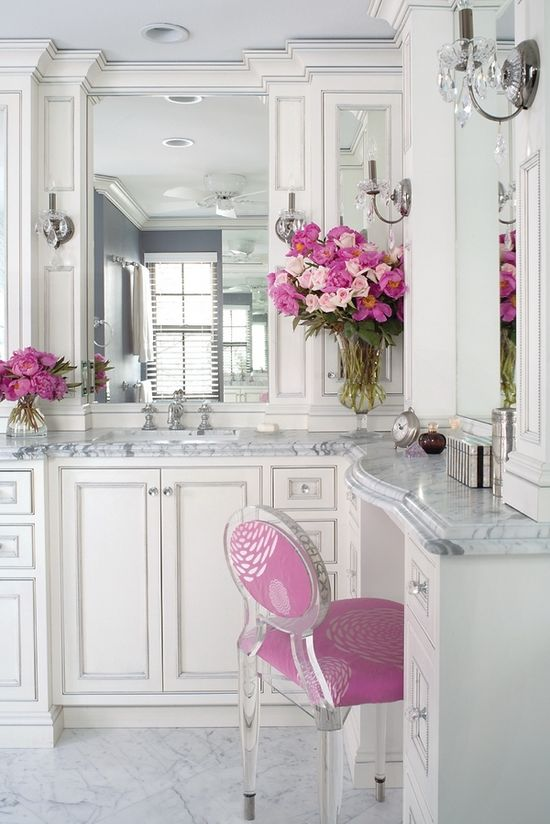 White and marble bathroom with pops of  pink.  Love the sconces!