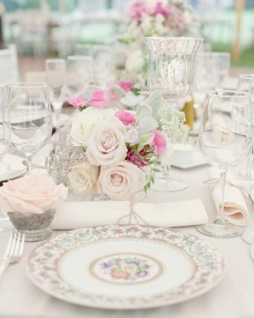 Small pink arrangements in crystal and mercury glass vessels were displayed on burlap table runners for a rustic yet glamorous look