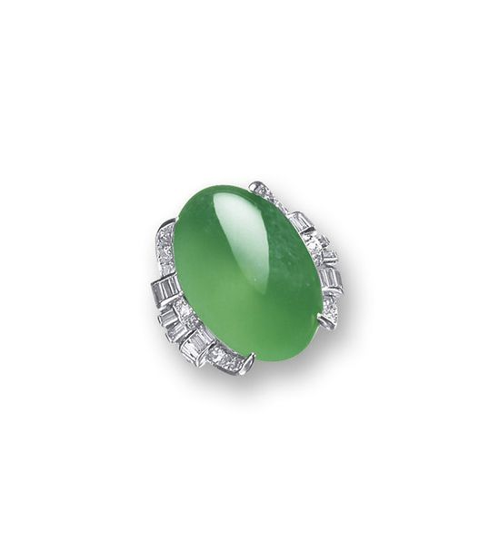 JADEITE AND DIAMONG RING. Centring on a bright emerald green oval jadeite cabochon of good translucency, to a stylised mount set with baguette and brilliant-cut diamonds, mounted in 14 karat white gold.  Cabochon approximately 23.32 x 15.61 x 10.00mm. LOT SOLD. 187,500 HKD