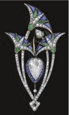 1920s Boucheron Art Deco brooch set with a pear shaped diamond surrounded by three lotus flowers with diamonds, sapphires and emeralds.