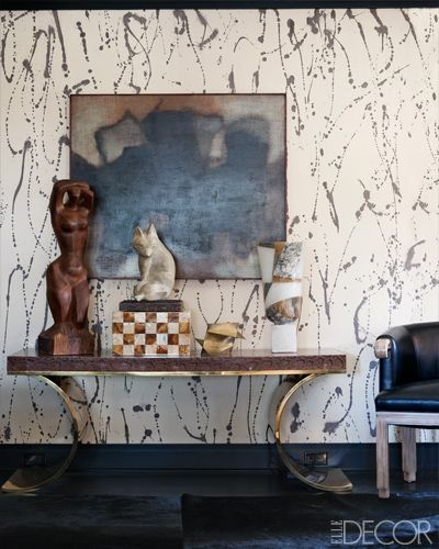 The home of Lara & Jeff Sanderson     HALLWAY    A snakeskin-and-brass console in the hallway outside the master bedroom; the wall is covered in a hand-painted Porter Teleo wallpaper. Designer: Kelly Wearstler