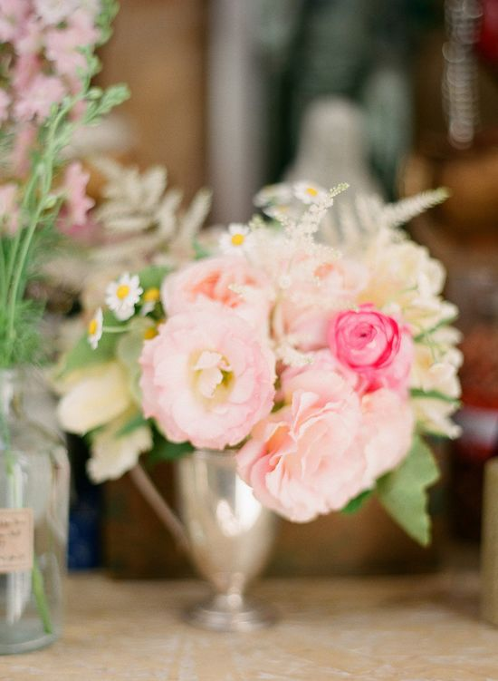 Soft florals arranged in silver trophy cups.