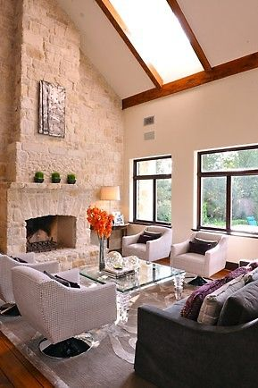 Stunning living room design with a white stone fireplace, large skylight and transparent coffee table. via porch.com