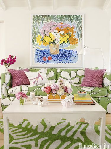 """Vibrant colors, a mix of patterns, and flowers everywhere — real, painted, and printed on the sofa — make this beach cottage living room """"cheerful, bright, and playful,"""" designer Krista Ewart says."""