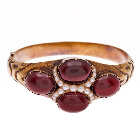 Gorgeous late Victorian bangle bracelet, circa 1910, featuring four large cabochon garnets and a bypass style pearl accent. Love the bold, almost Boho vibe.