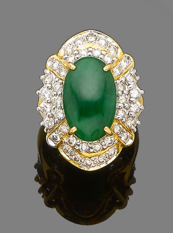 A jade and diamond cluster ring  The oval-shaped jade cabochon, within a brilliant-cut diamond surround and shoulders