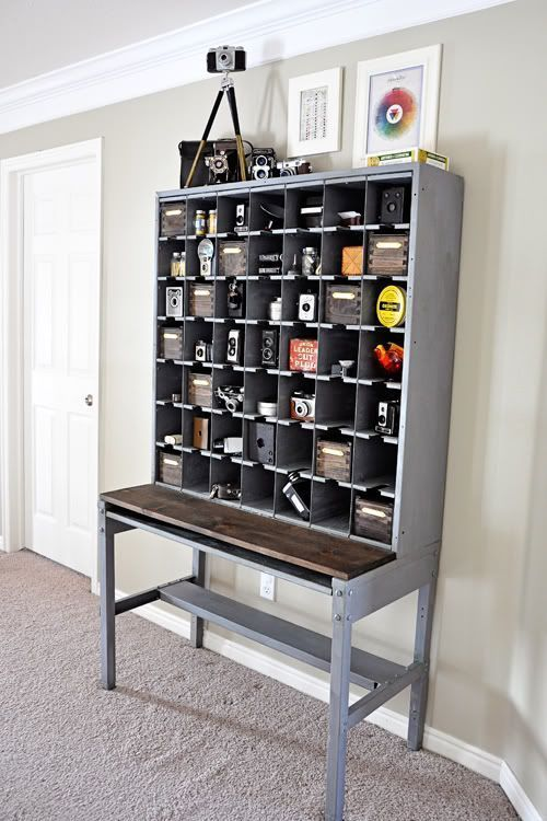 vintage mail sorter turned camera collection display. LOVE the dark wood plank against the grey, and the handmade dovetail joint