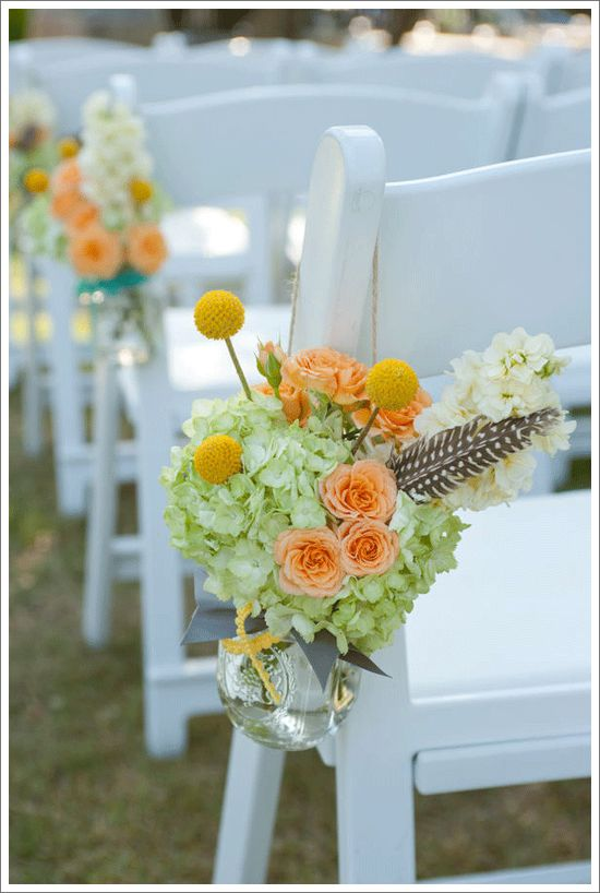 I like the idea of simple flower arrangements along white chairs, looks colonial