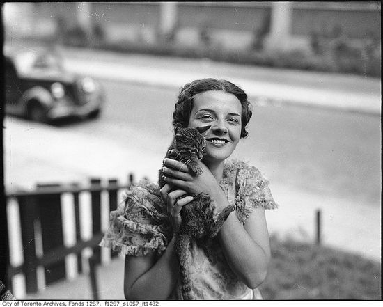 Billie Hallam, Miss Toronto 1937, posing with a kitten in the front yard of her home, 191 Booth Avenue, Toronto, c. 1937. #vintage #Canada #1930s #cats #pets
