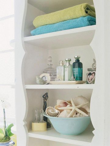 Seaside Elegance-If you want to add a subtle touch of the ocean to the bathroom, shells are the perfect accessory. This bowl of pretty neutral shells displayed on the bathroom's exposed shelf looks simple, classic, and clean.