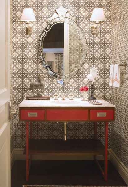 patterned wallpaper, decorative frameless glass mirror, and a red campaign desk vanity.