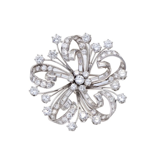 A diamond brooch/pendant  of floral motif, centering a round brilliant-cut diamond cluster center within openwork petals of round brilliant and baguette-cut diamonds; estimated total diamond weight: 11.00 carats; mounted in platinum; diameter: 1 7/8in.