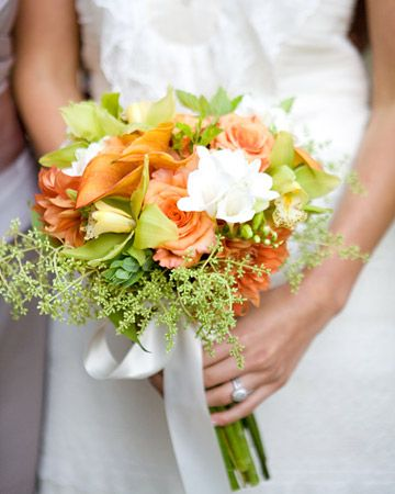 A bouquet of citrus-hued blooms included dahlias, privet berry, cymbidium orchids, and freesia