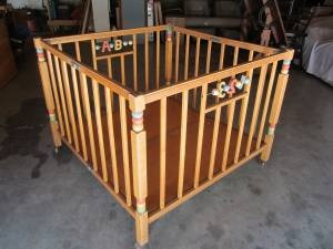 Wooden playpen with spinner toys on the side.