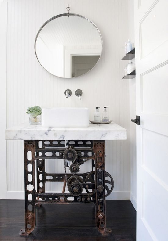I don't know if the base of this sink is reclaimed industrial, or new-made-to-look-industrial, but the juxtaposition of the classic marble top with the industrial base is super-cool.  By Antonio Martins Interior Design.