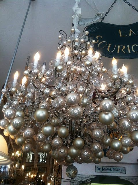 silver christmas ornaments hanging from a chandelier