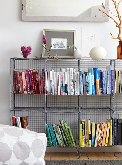 wire bookshelves with color coordinated books//I like this.