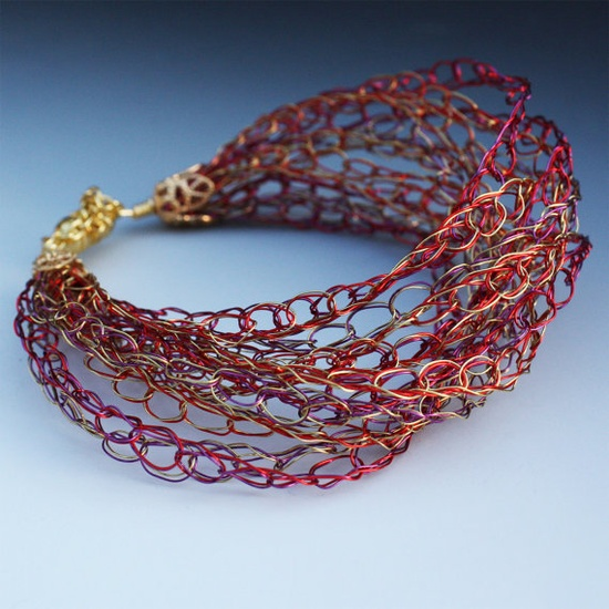Elegant, colorful, and light, this bracelet was crocheted using several strands of very thin color wire (red, magenta, gold).    Contemporary artisan jewelry in mixed media by Aliona K