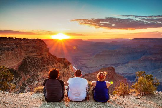 friends watching sun set at grand canyon