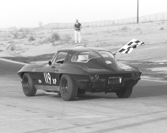 Classic black and white picture of an original 1963 C2 Z06 Chevrolet Corvette flying the checkered flag. The L84 V-8 327 cu in engine in the early Z06 was rated a 360 horsepower. The L84 327 Corvette engine had the capability for more horsepower, but they were shipped with restrictive factory exhaust manifolds in order to compete in the Sports Car Club of America production racing classes.