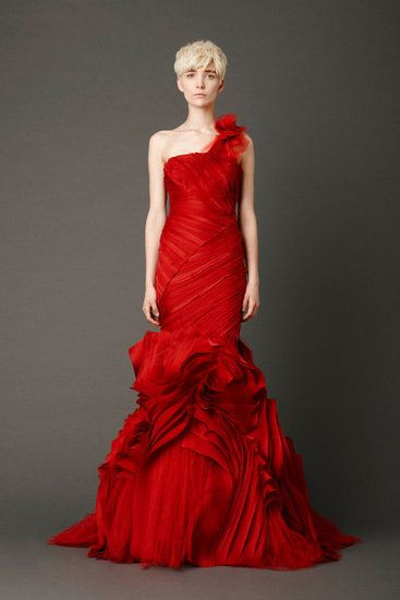 Scarlet mermaid gown with tiered, micro-bias bodice and inverted flange skirt with abstract floral shoulder corsage detail.
