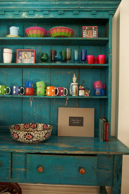 Colorful mugs and plates act as decoration on open shelves.