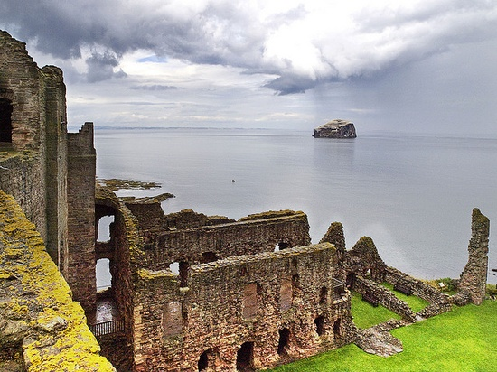 Bass Rock from Tantallon Castle. The ruins of Tantallon Castle sits on a promontary overlooking the Bass rock , an island in the Firth of Forth. The bass rock has a lighthouse and is now a bird sanctuary and home to thousands of gannets
