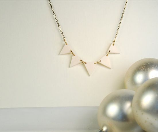 white triangles on gold necklace
