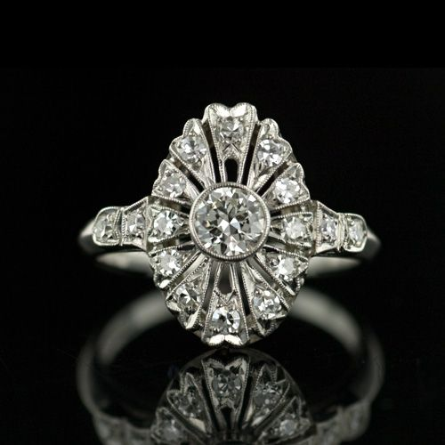Art Deco Diamond Ring    This gem of a ring has a pleasing marquise shape and is centered with a .30 carat European cut diamond. Small accent diamonds are set in slight petal shapes surrounding the center diamond amidst delicate pierced detailing.
