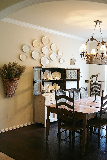 Vintage white/cream platters hung on the wall in dining area of the kitchen. From The Farmhouse Porch