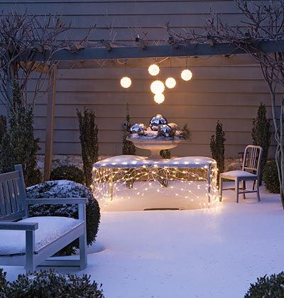 Set the Table  Draped over a picnic table, an inexpensive set of net lights (intended for hedges) twinkles beneath a cover of fresh snow, creating an almost polka-dot effect.