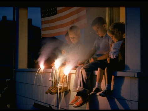 Boys Sitting on Porch Holding Sparklers, with US Flag in Back, During Independence Day Celebration
