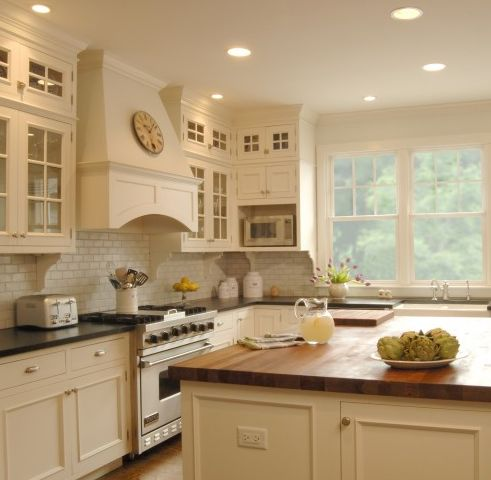 soapstone & butcher block counters with cream cabinets & subway tile backsplash
