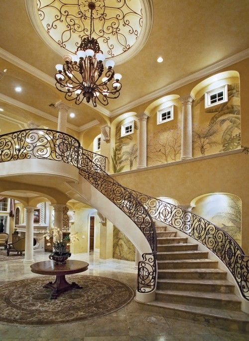 What a lovely, grand, opulent entry, staircase, wrought iron railing work and ceiling.