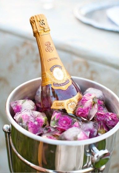 chill champagne in a bucket full of rose ice cubes for a summer party
