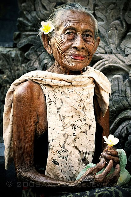 Elderly Balinese lady selling flowers at a temple.