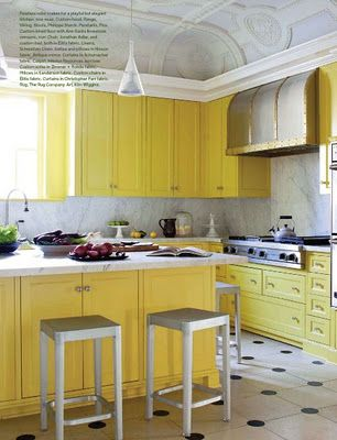 Yellow cabinets bring a bright pop of colour to an otherwise neutral kitchen. Look at that ceiling!