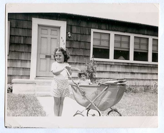 Vintage snapshot of little girl with doll in carriage circa 1940's.
