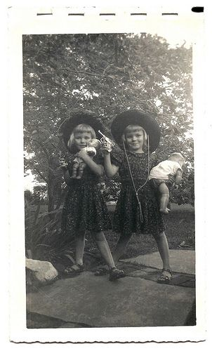 Cowgirls. Twin little girls with cowgirl hats, toy pistols and dolls. Vintage photo from around 1950.