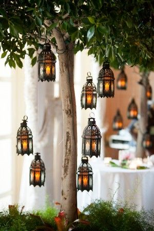 Old World hanging lanterns in trees lit this tropical beach wedding