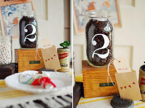 Mason jar table numbers filled with coffee beans. #MarthaStewartWeddingsMAgazine