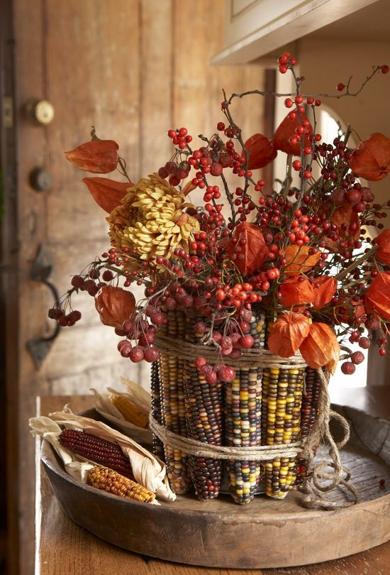 DiY Indian Corn Vase ::: Wrap a can with rubber bands.  Then remove the husks from corn and simply slide the corn cobs in standing them upright. Cover the rubber bands with twine & fill with fall flowers like dahlias, mums, berries and asters!