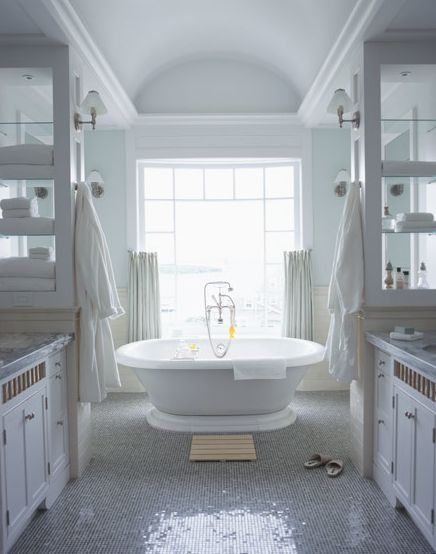 Gorgeous master bathroom with tub, soft green blue silk drapes, chrome sconces, double sinks with marble countertops, chair rail, beadboard, shiny tiled floors, sconces, white bathroom vanities and green blue walls paint color.